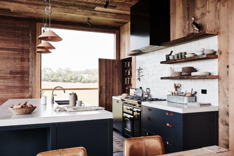 La cucina è in blu marino e bianco, con maniglie in pelle e alzatina in piastrelle bianche