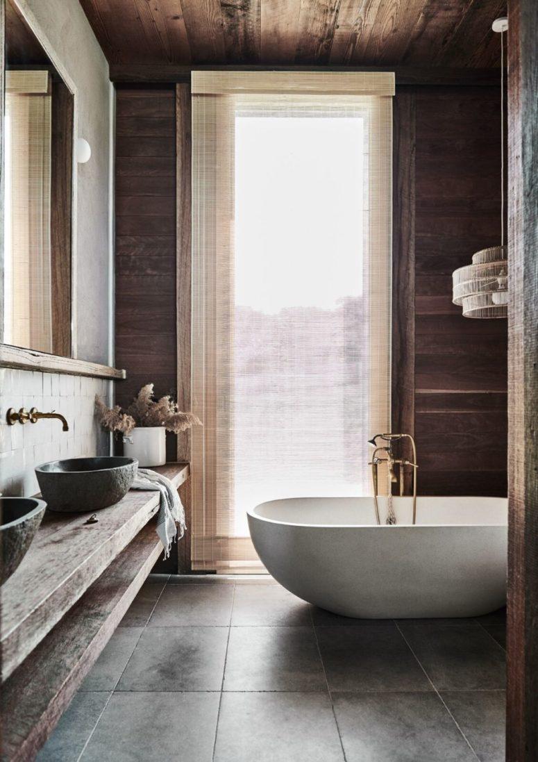 Questo bagno presenta molto legno naturale, piastrelle, una vasca in pietra bianca e persino alcune viste