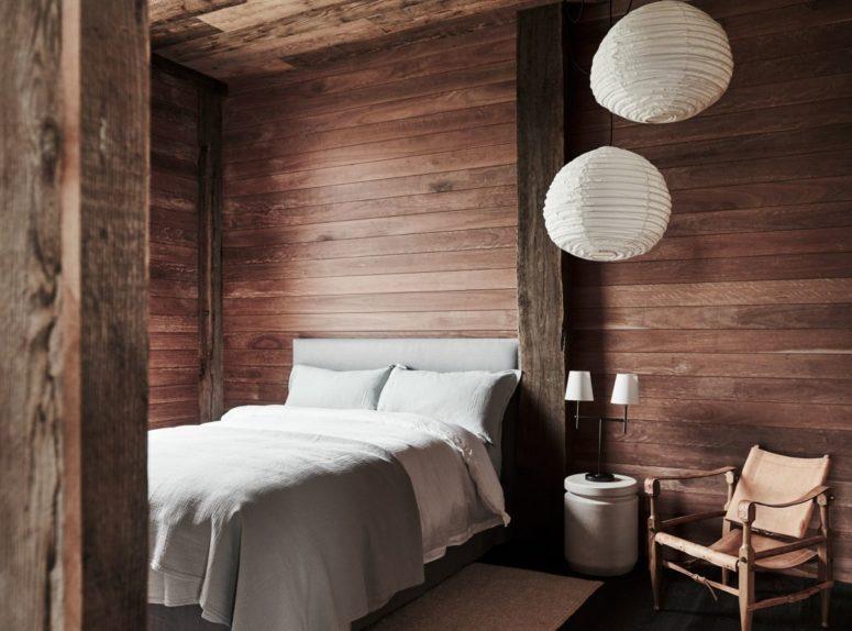 Questa camera da letto è completamente rivestita in legno, c'è un comodo letto, alcune lampade di carta e una sedia in pelle