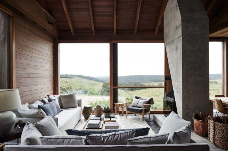 Il soggiorno presenta una parete vetrata, mobili in legno e comodi divani attorno a un focolare in cemento