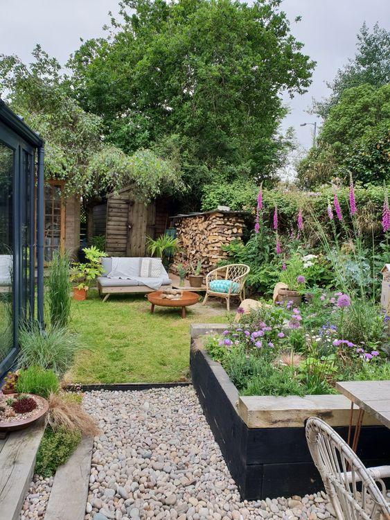 un piccolo e accogliente giardino con un'aiuola, alcune fioriture luminose in vaso e non solo, un prato e alcuni mobili da giardino