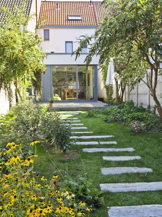 un piccolo giardino sul retro con un prato verde, vegetazione e fiori luminosi e alcuni alberi più un marciapiede