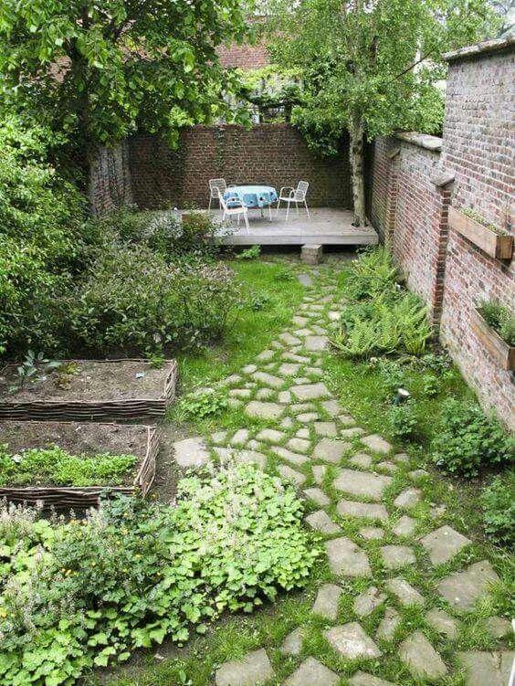 un piccolo giardino sul retro con un prato verde, alcune aiuole, vegetazione e arbusti più un paio di alberi