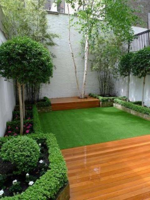 un piccolo ed elegante giardino con prato verde, con alcune aiuole fiorite e verde e arbusti e alberi