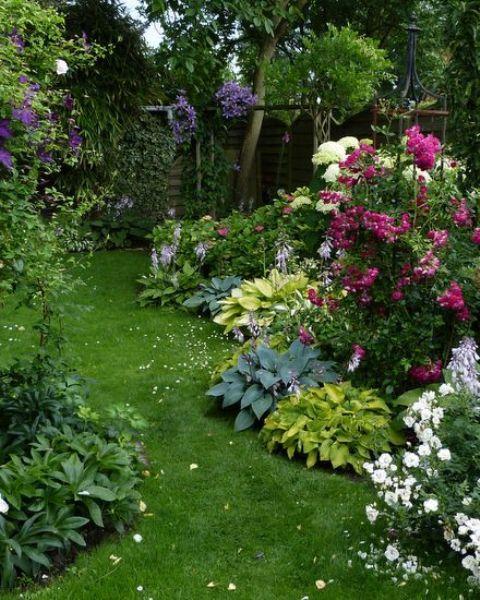 un piccolo giardino colorato con un prato verde, alcuni arbusti, fioriture luminose, diversi alberi nell'angolo