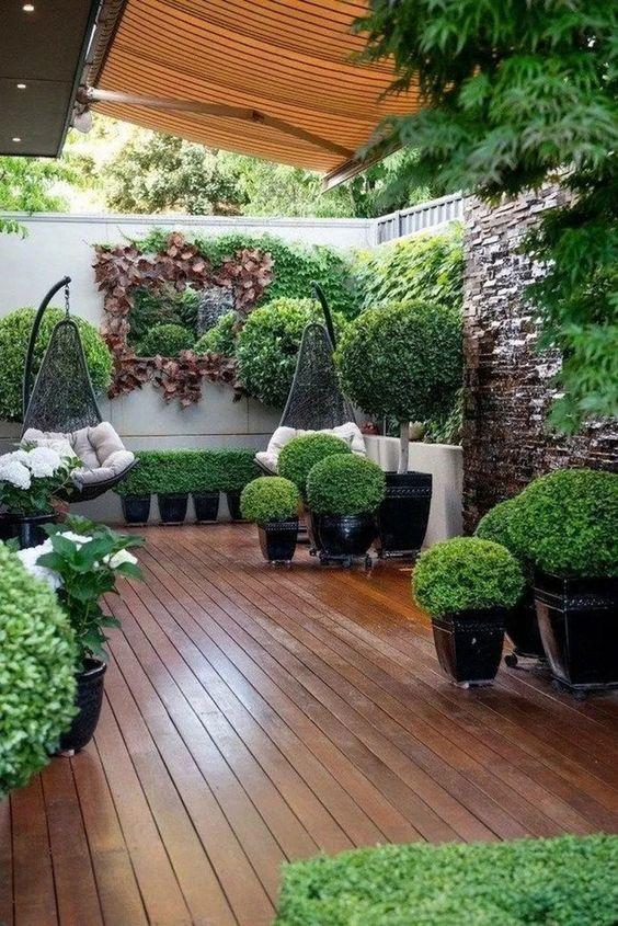 un piccolo giardino contemporaneo con tanto verde in fioriere, alcuni arbusti, verde sui muri e sedie sospese