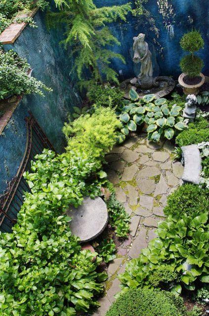 un piccolo angolo del giardino con una statua vintage, un po 'di verde in vaso, una panchina e tanto verde intorno