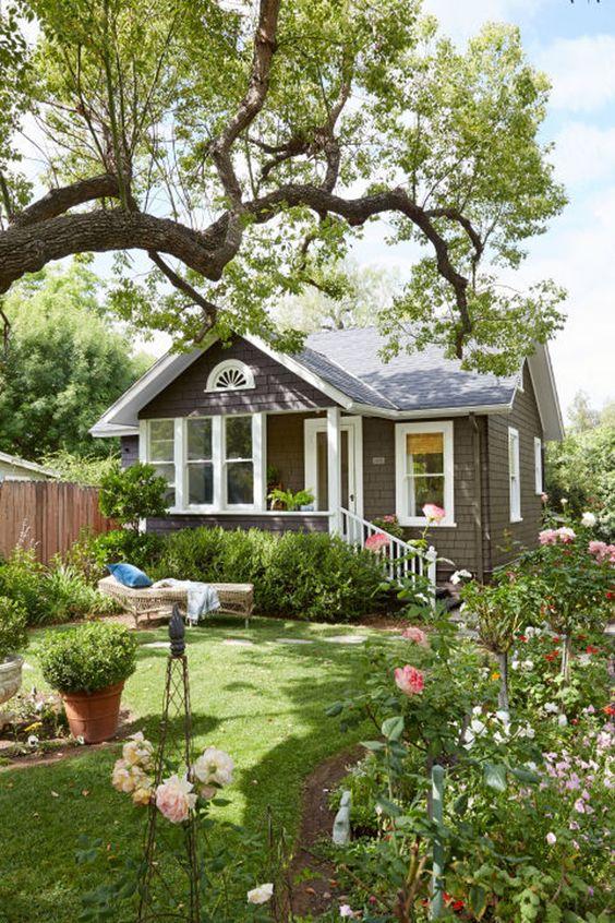 un piccolo giardino chic con fiori e vegetazione, con un prato ben curato, un po 'di verde in vaso e un grande albero