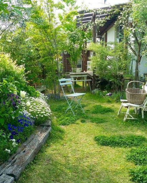 un piccolo giardino con prato, un'aiuola con fioriture luminose, alcuni mobili da giardino vintage e alcuni arbusti e alberi