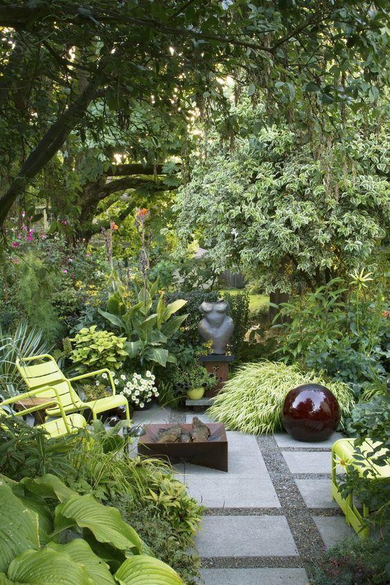 un piccolo giardino lussureggiante con molte erbe, arbusti e fiori, alcuni alberi, un pozzo del fuoco e sedie da giardino