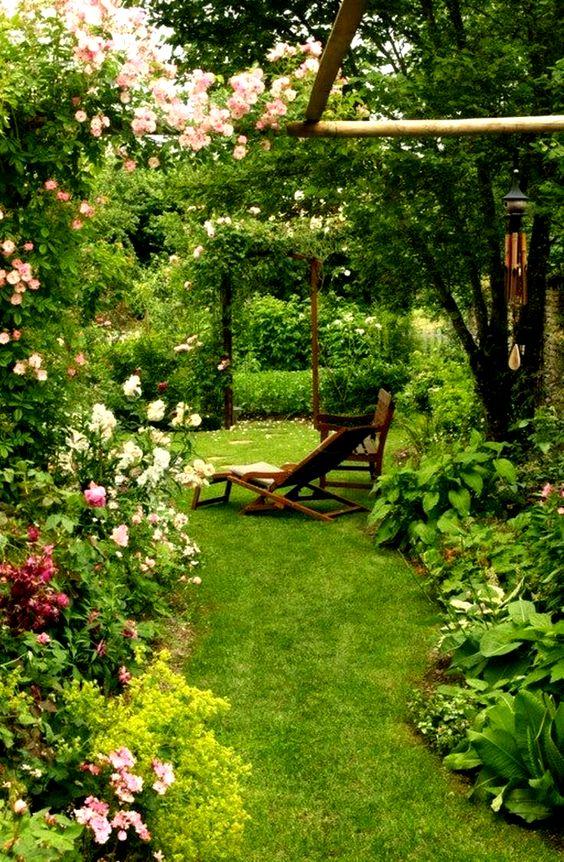 un piccolo ma molto rigoglioso giardino con prato curato, vegetazione, fiori rosa e un arco con vegetazione rampicante e fioriture