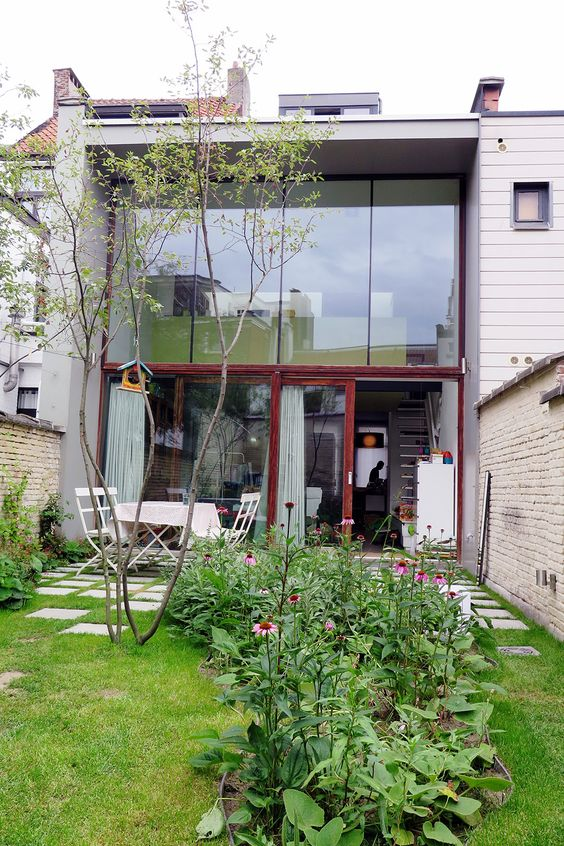 un piccolo giardino moderno con un prato, un albero, alcuni fiori e vegetazione e un set da pranzo bianco è molto semplice e carino