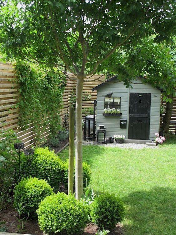 un piccolo ma elegante giardino sul retro con un prato verde, alcuni arbusti e un albero più un muro con vegetazione rampicante