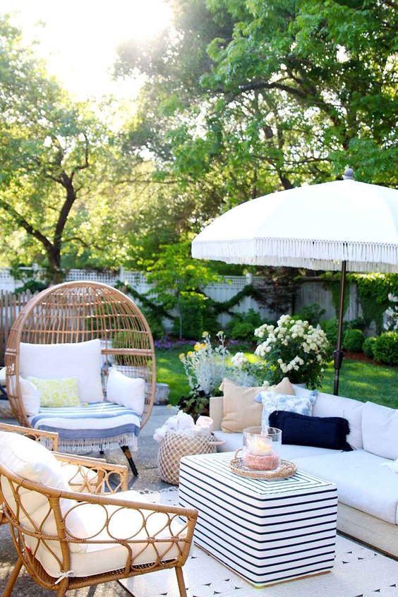 un piccolo e accogliente patio estivo con mobili neutri, sedie di vimini, tessuti stampati, cesti e un ombrello bianco sopra lo spazio