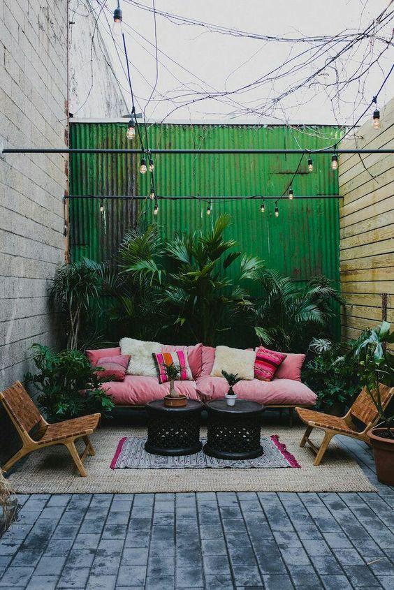 un luminoso cortile interno tropicale con un divano rosa e cuscini stampati, sedie in pelle, molte piante rigogliose in vaso e tavoli neri