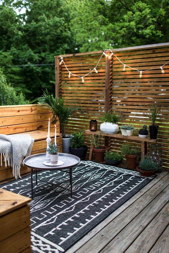 un cortile interno nordico tutto rivestito di legno, con un tappeto stampato, alcune piante in vaso e lanterne e luci a candela