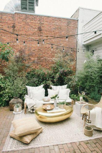 un piccolo cortile interno chic con un tappeto, alcuni cuscini, piante in vaso, cesti e mobili in legno e vimini