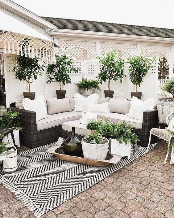 un piccolo ed elegante patio in una combinazione di colori monocromatici, con un tappeto stampato, un divano in vimini, piante in vaso e alcuni cestini