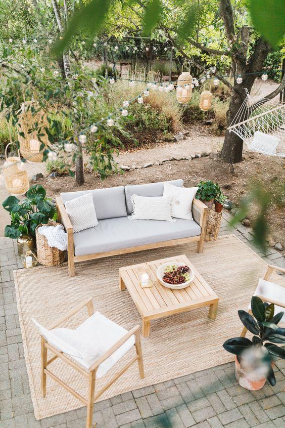 un piccolo patio contemporaneo con mobili bianchi e grigi, un tavolo in legno, alcune piante in vaso, luci e lanterne a candela