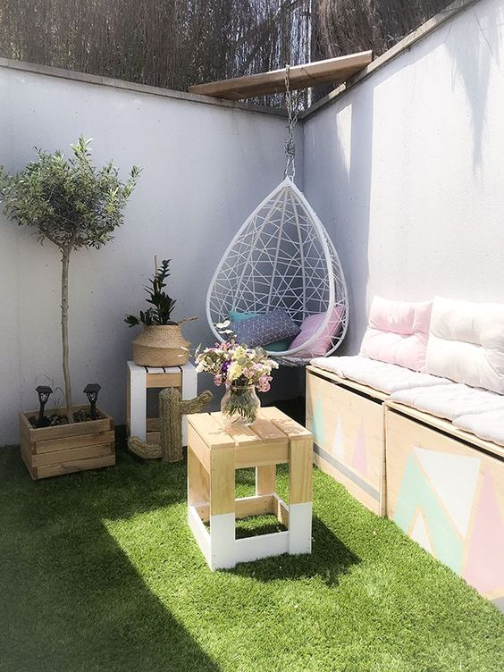 un piccolo e divertente cortile con prato, con un divano contenitore, alcuni tavolini, piante in vaso e una sedia a forma di uovo pendente