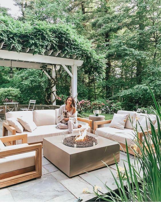 un piccolo patio contemporaneo con semplici mobili neutri, un grande focolare e un po 'di verde e fiori intorno