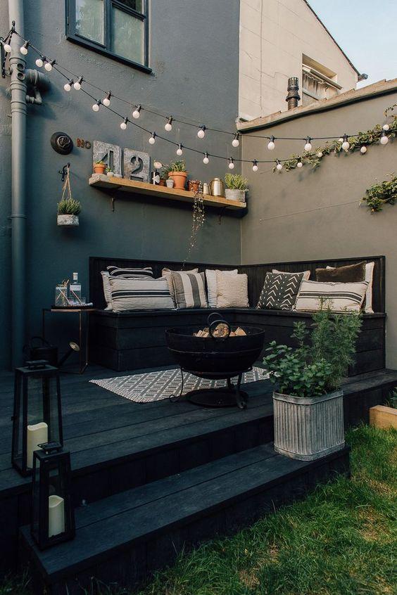 un piccolo cortile nero con un divano incorporato, piante in vaso, luci sullo spazio e cuscini stampati più un pozzo del fuoco
