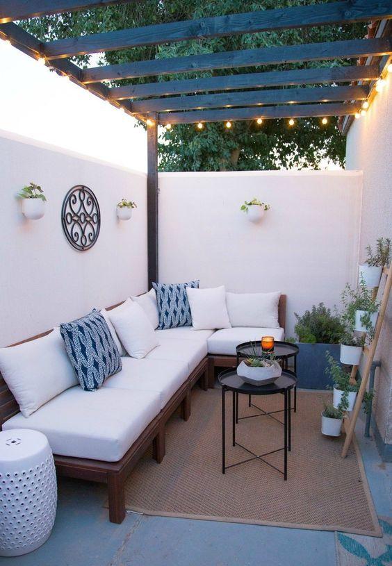 un piccolo e grazioso cortile con un divano ad angolo, tavolini, piante in vaso, tavolini e alcune luci nello spazio