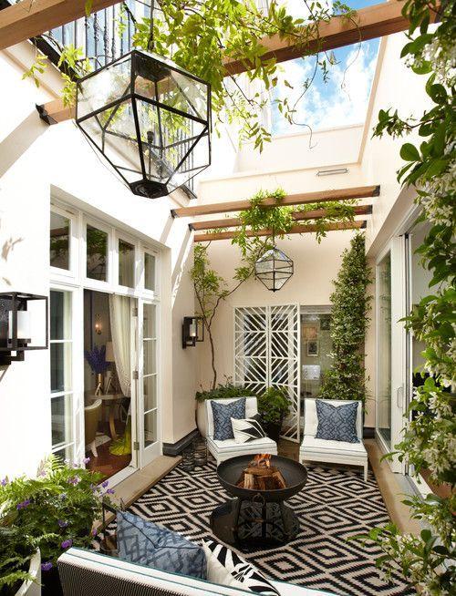 un piccolo cortile interno contemporaneo in una combinazione di colori monocromatici, con un tappeto stampato, cuscini blu, molta vegetazione, lanterne accattivanti e un pozzo del fuoco