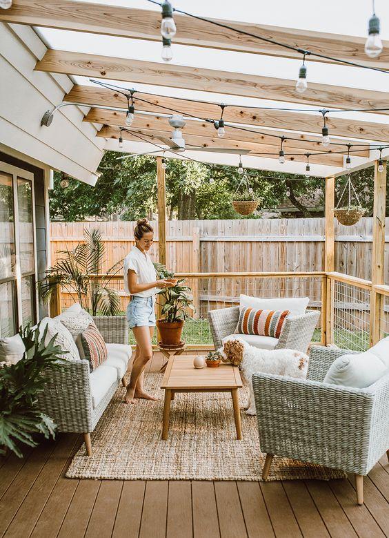 un piccolo terrazzo neutro con mobili in vimini, un tappeto di iuta, luci e piante in vaso e tessuti stampati