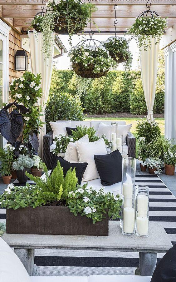 un piccolo terrazzo monocromatico con un tappeto a righe, un divano nero, una panchina, candele e tanto verde e fiori bianchi