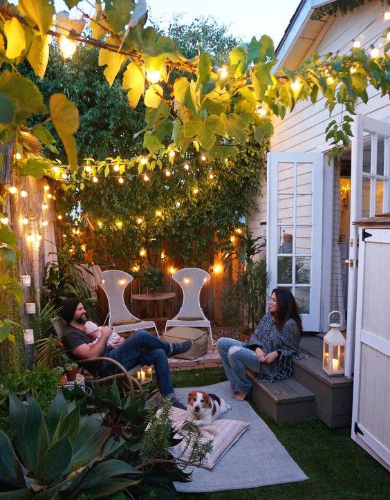 un piccolo cortile accogliente con un paio di sedie e pouf, alcuni tappeti e un cuscino e molte luci sopra
