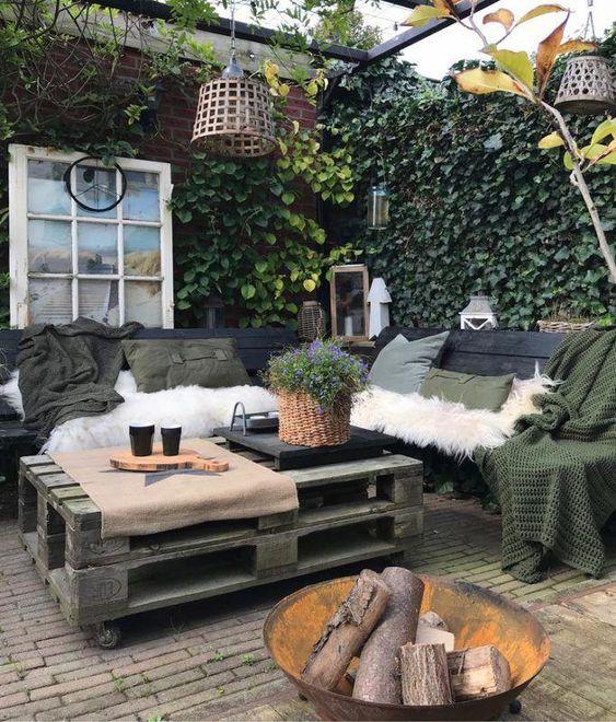 un piccolo cortile nordico con mobili in pallet, tessuti scuri, rivestimenti in pelliccia sintetica, lampade a sospensione, vegetazione in vaso e un pozzo del fuoco