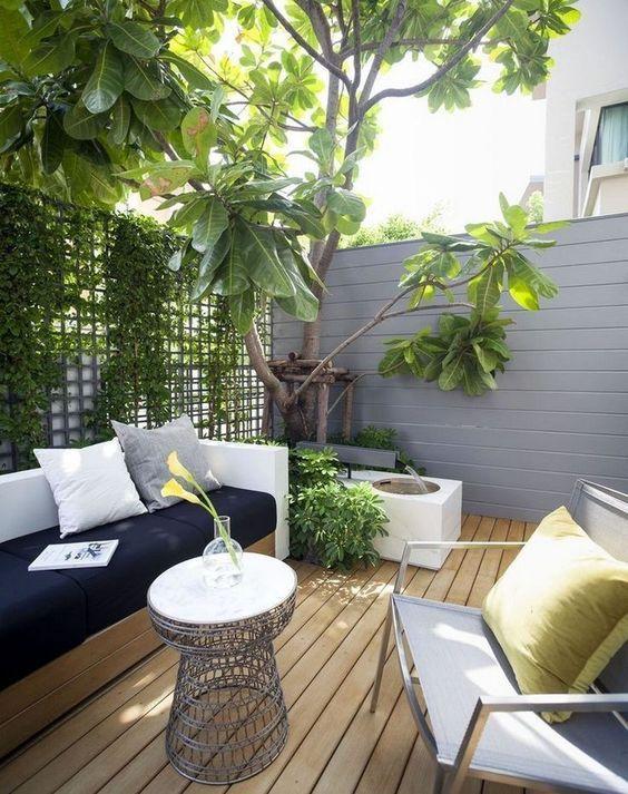 un piccolo cortile interno monocromatico con mobili e tessuti in bianco e nero, un tavolino, una cascata e un muro verde
