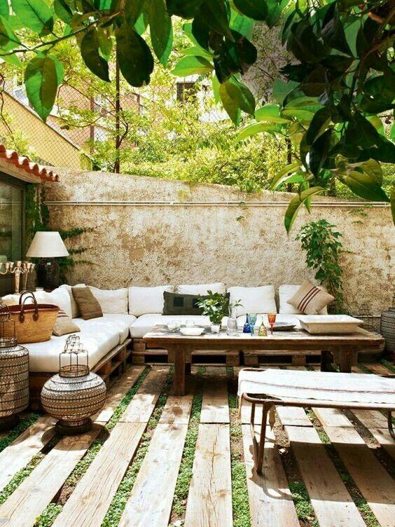 un piccolo cortile con un divano ad angolo, un tavolo in legno, lanterne a candela di vimini, un pavimento in assi di legno e un po 'di verde