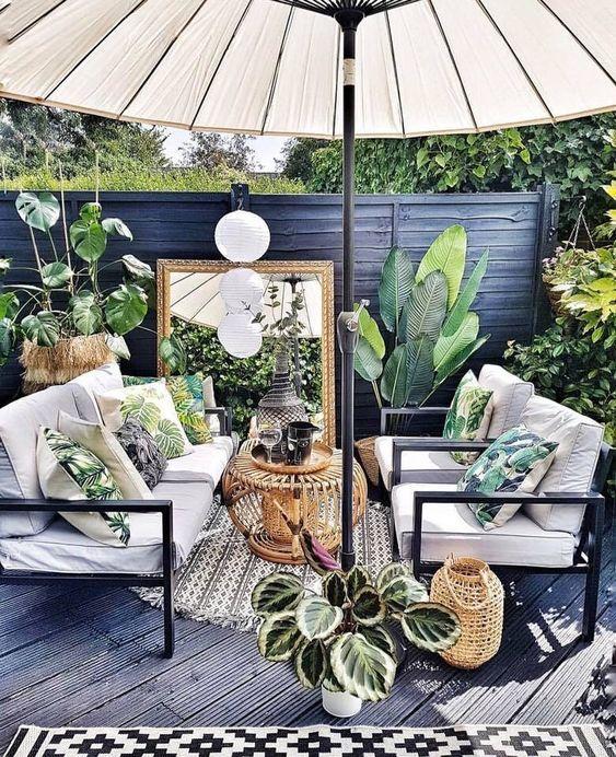 un piccolo patio tropicale in nero e grigio, con mobili bianchi, un grande ombrellone, piante in vaso e cuscini tropicali