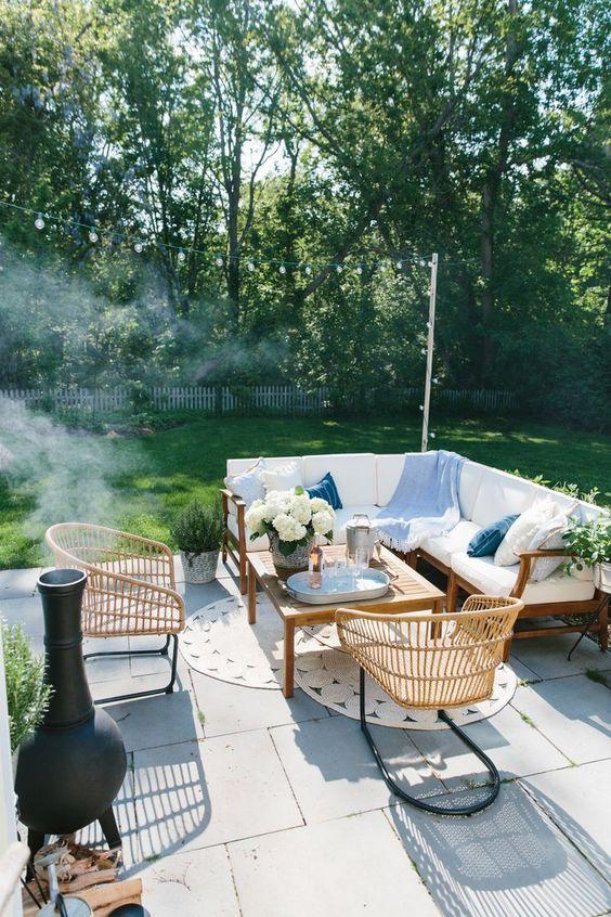 un piccolo patio esterno con un divano ad angolo bianco, sedie di vimini, tappeti di iuta, un focolare e alcune fioriture e vegetazione in vaso