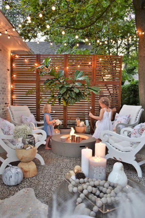 un piccolo cortile con pavimento in piastrelle, un pozzo del fuoco in cemento, sedie vintage, un albero in vaso, luci, candele e fiori