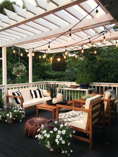 un piccolo ma accogliente patio con divano e sedie, pouf in pelle, fiori in vaso e vegetazione, luci e lanterne a candela
