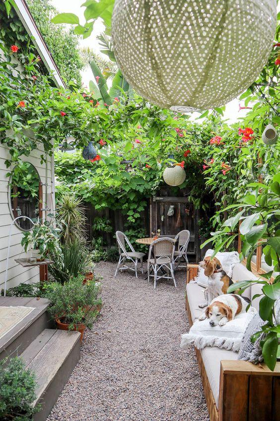 un cortile piccolo ma molto lussureggiante con un divano, lampade a sospensione, un sacco di fiori verdi e rosa e un piccolo set da pranzo