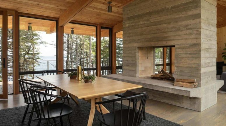 C'è anche uno spazio da pranzo più formale con sedie nere e un camino a doppia faccia che divide gli spazi