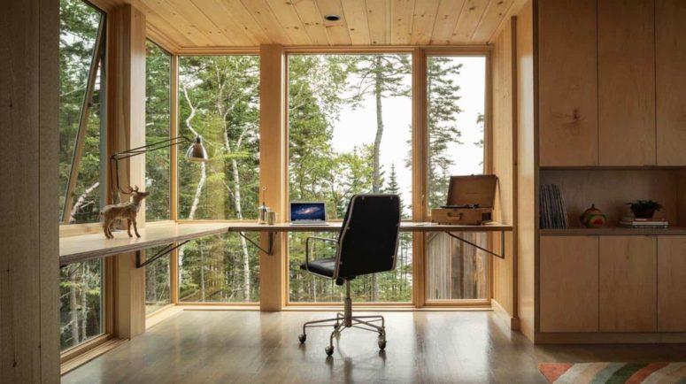 Questa moderna scrivania sospesa sfrutta appieno le finestre dal pavimento al soffitto e l'abbondanza di luce naturale