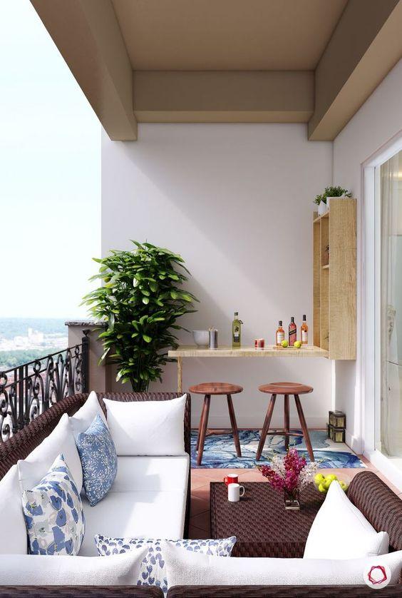 un balcone audace con mobili in vimini scuro, un piccolo bar Murphy e sgabelli più una pianta in un angolo