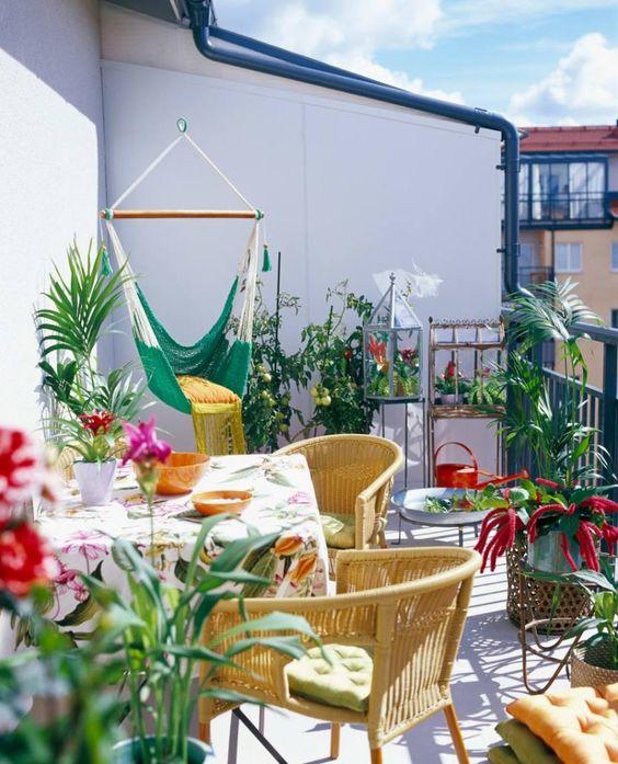 un colorato balcone estivo con sedie gialle, tessuti stampati, una sedia amaca verde e molta vegetazione e fiori in vaso