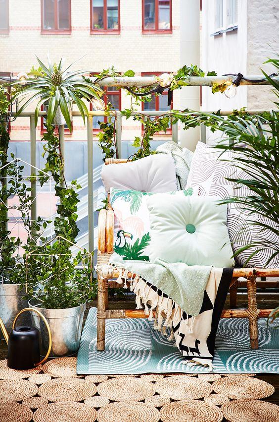un luminoso balcone estivo con un divano in rattan, tessuti stampati, vegetazione in vaso e tappeti a strati sembra molto tropicale
