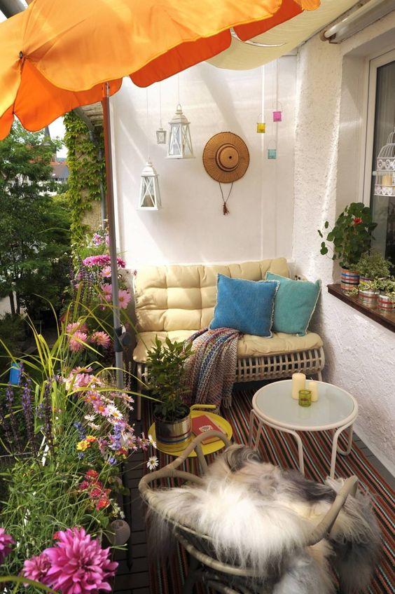 un luminoso balcone estivo con tessuti audaci, mobili in rattan e metallo, lanterne colorate a candela e un ombrello più fiori in vaso
