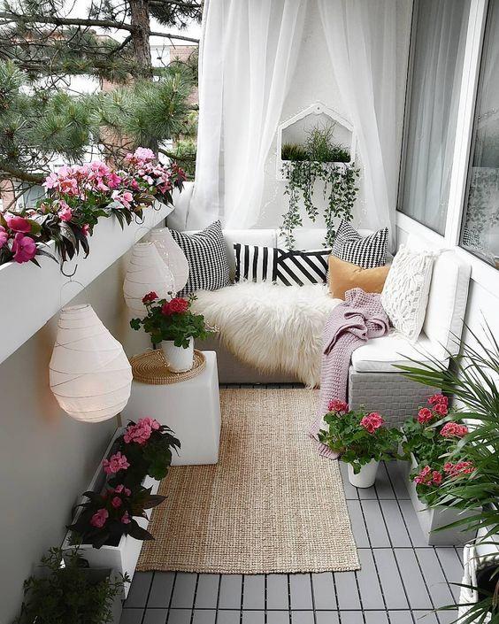 un elegante ma piccolo balcone estivo in bianco, con tende trasparenti, un tappeto di iuta, fiori in vaso, lanterne di carta e tessuti stampati