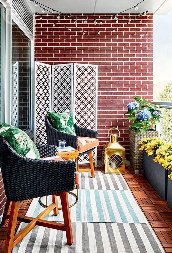 un balcone luminoso ed elegante con tappeti a strati, sedie di vimini e cuscini stampati, fiori in vaso e una grande lanterna a candela
