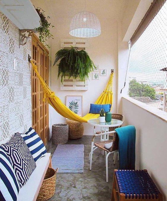 un balcone estivo luminoso e allegro in giallo e blu, con tessuti stampati e solo luminosi, un'amaca gialla e un po 'di verde