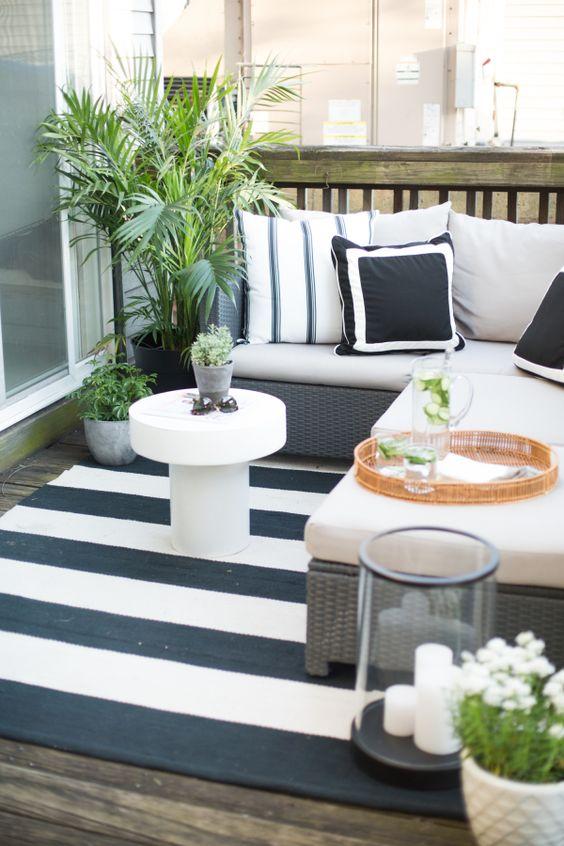un accogliente balcone monocromatico con tessuti stampati, vegetazione e fiori, lanterne a candela e mobili in vimini
