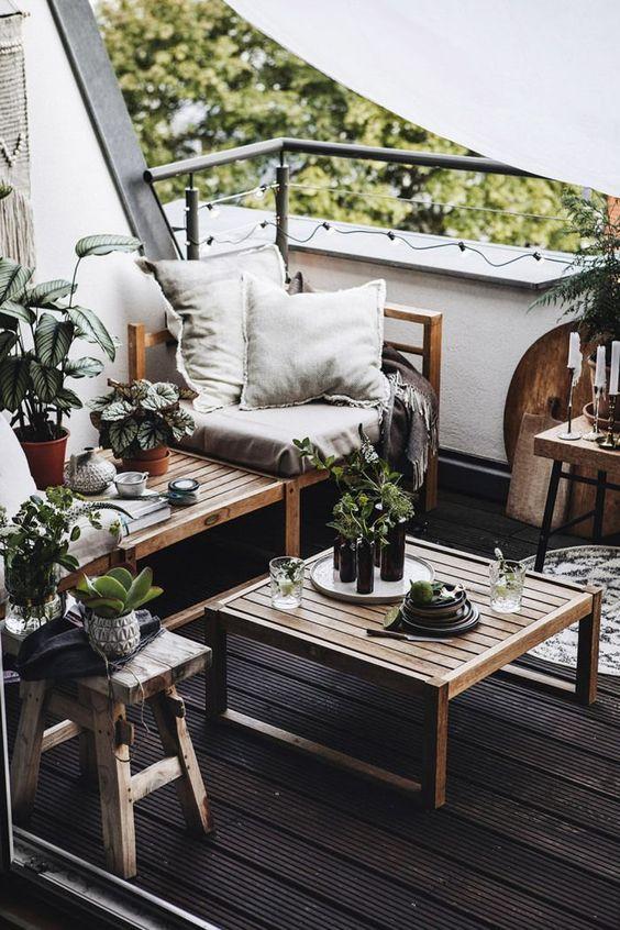 un balcone monocromatico con un pavimento nero, mobili in legno naturale, tessuti neutri, piante in vaso e candele